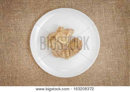 Linen background with boiled pork on plate.