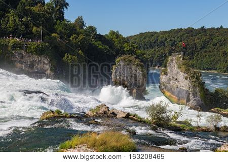 Waterfall on the river Rhine Schaffhausen Switzerland. Rhine Falls is the largest waterfall in Europe in summer day against blue sky