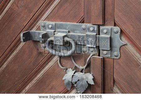 Vintage iron door lock - heck with knocker on the wooden brown door
