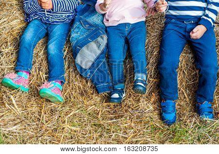 Children in jeans posing in the hayloft