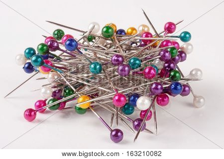 pile of of multi-colored sewing pins on a white background.