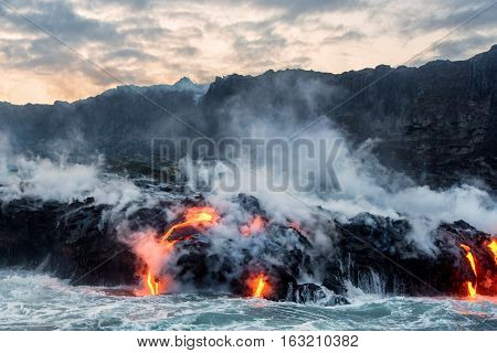 Molten lava flowing into Pacific Ocean from the Kilauea lava flow on Big Island of Hawaii under partly cloudy skies