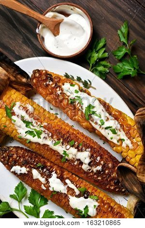Bbq corn with green herbs and sauce top view
