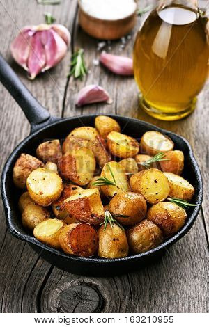 Baked potato in frying pan on wooden background