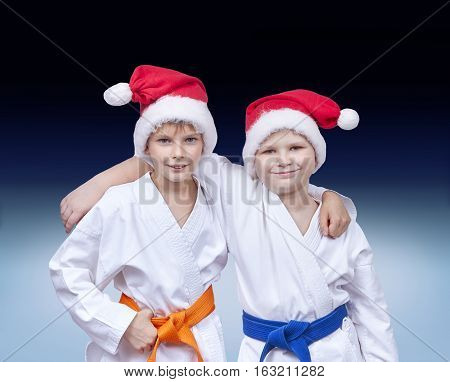 Children athletes in caps of Santa Claus on a gradient background