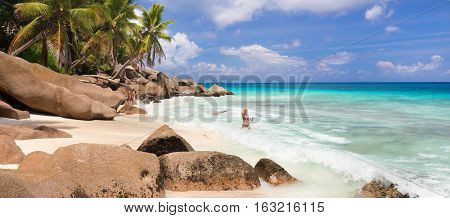 Active sporty woman wearing stylish bikini enjoying swimming and snorkeling at amazing on Anse Patates beach on La Digue Island, Seychelles. Summer vacations on picture perfect tropical beach concept.