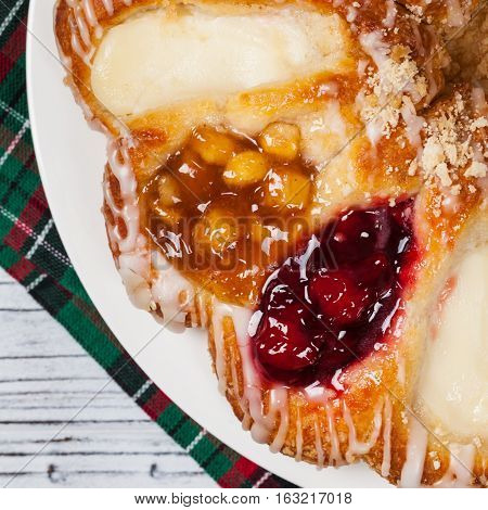 Danish Pastry with Cherry, Apple fruit and Cheese fillings. Selective focus.