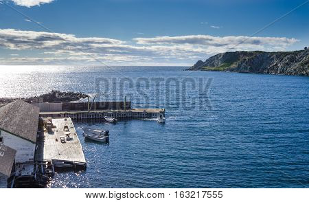 boats at a cliff-side dock house in Twillingate, Newfoundland, man works on the engine of one of 4 boats tied up to a wooden, cliff-side dock house for the day,
