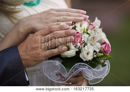 hands of bride and groom with wedding rings on a bouquet of roses