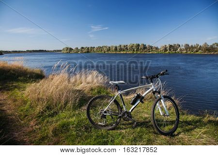 beautiful view of the river a mountain bike is on a background of the river on a clear sunny day bike in the nature blue water and sky
