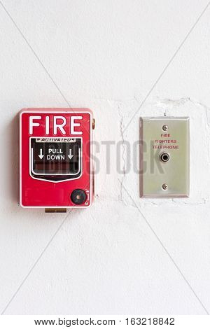 Fire alarm switch and fire fighters telephone on factory wall