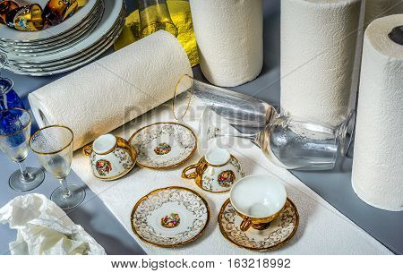 Four rolls of paper towels one of them is prepared. On a long threadbare cloth are cups and saucers. Glasses and the glass still with water droplets.