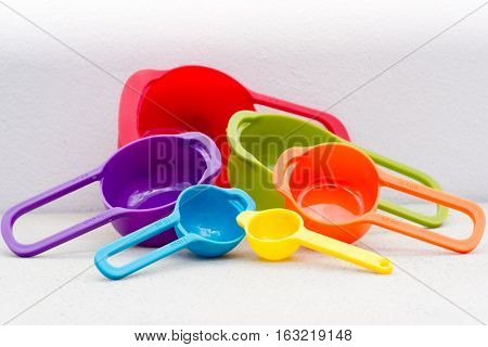 The colorful measuring cups on white background