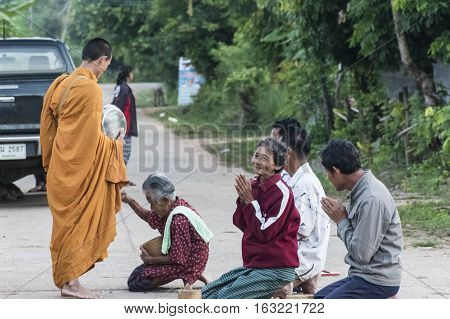 Buddhist give alms to a Buddhist monk Ban Namon Kalasin province Thailand in the morning on November 12 2016.