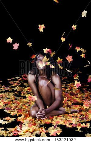 Attractive African American Woman Sitting Implied Nude Among Silk Autumn Leaves In Studio Throwing Them