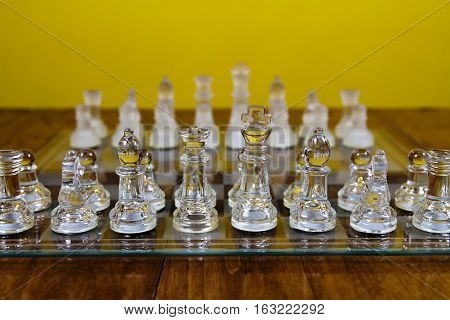 Glass Chess Pieces Set Up On Board In Starting Position Sitting On Wood Table With Yellow Wall