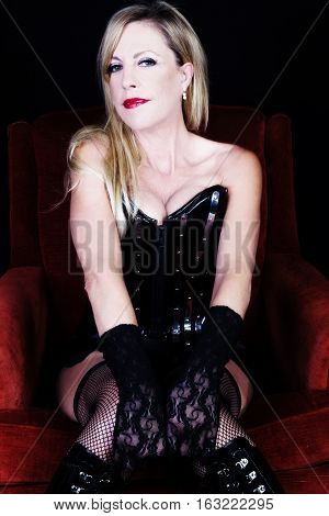 Older Caucasian Blond Woman Sitting On Red Chair In Black Corset Fishnet Stockings Lace Gloves Showing Cleavage