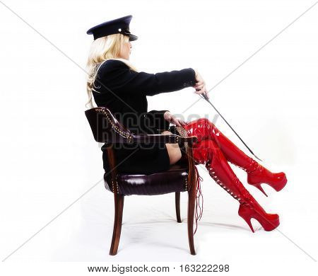 Older Caucasian Woman Sitting In Chair With Red Boots Jacket And Hat With Riding Crop