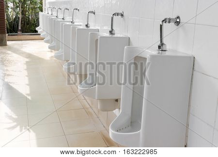 Closeup urinals white color in men's public restroom with light of sun