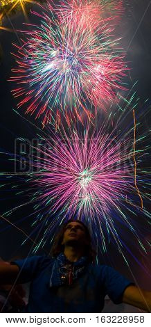 Young man is looking up to the sky for Colorful Fireworks
