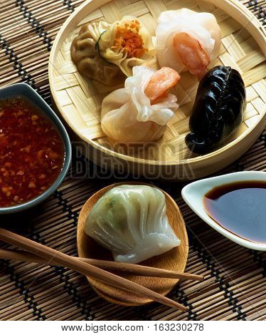 Assorted Dim Sum in Bamboo Steamed Bowl and Hagao with Shrimp on Wooden Plate with Red Chili and Soy Sauces and Chopsticks closeup on Straw Mat background