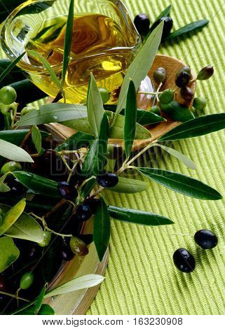Olive Oil in Glass Gravy into Branches of Raw Green and Black Olives with Leafs in Wooden Bowl closeup on Green Textile background