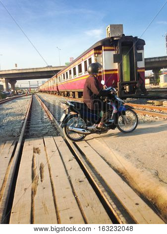 Man driving motorcycle crossing railroad risk when crossing rails.