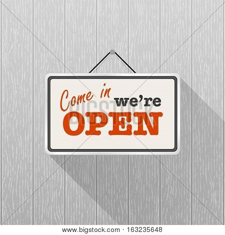 Simple white sign with text 'Come in we're open' hanging on a gray wooden wall. Wood texture with vertical stripes rustic panels. Creative business interior template for shop store supermarket.