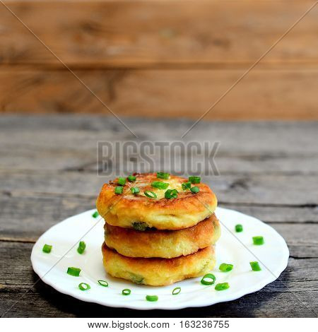 Mixed vegetable patties on a plate isolated on wooden background. Fried patties cooked of potatoes, green peas, carrot and green beans and garnished with fresh green onion. Delicious vegetable dish