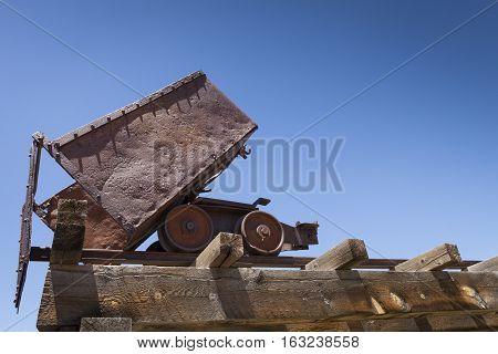 Old rusty mining ore cart on trestle under blue sky.