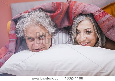 Adult Couple Relaxing In Bed At Home
