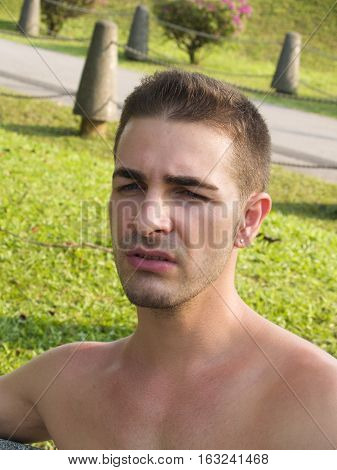 A young man sitting outdoor looking at something faraway