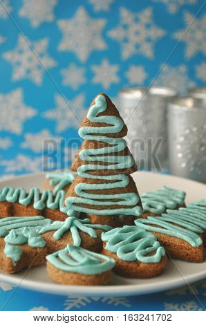 Decorated Christmas honey cookies on blue winter background with snow flakes and tea lights