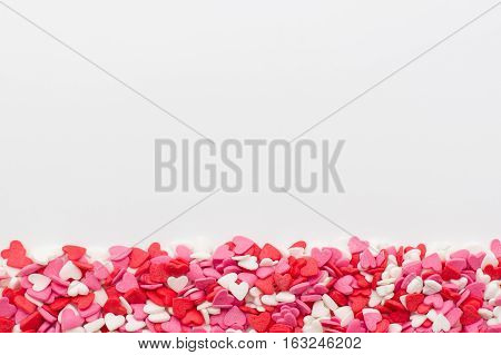 many little hearts at the bottom on a white background. festive background for Valentine's day birthday holiday