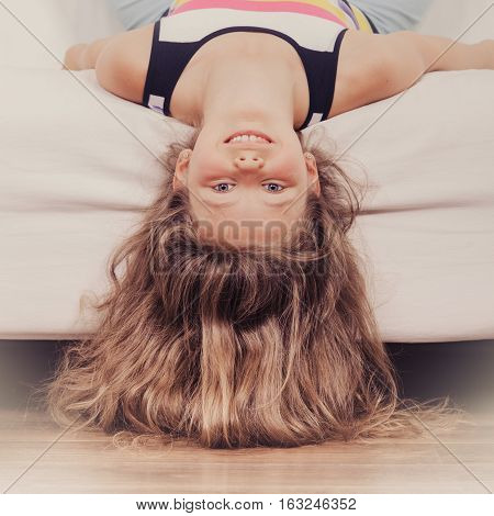 Happy little girl with long hair lying upside down on sofa at home. Kid playing having fun on couch.