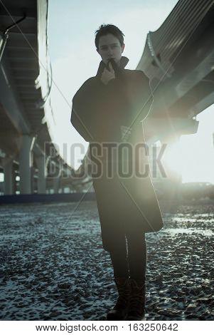 Young stylish woman urban walking under bridge