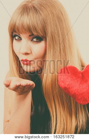 Woman elegant blonde long hair girl dark makeup red lipstick holding red heart love symbol flirting sending kiss. Valentines day happiness concept
