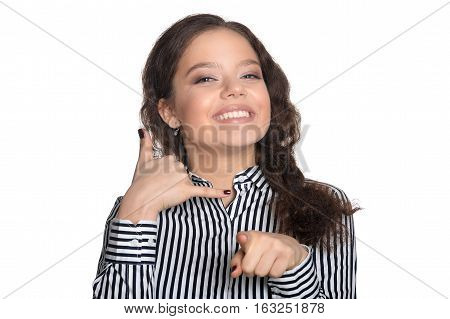 Portrait of young woman showing call me gesture isolated on white background