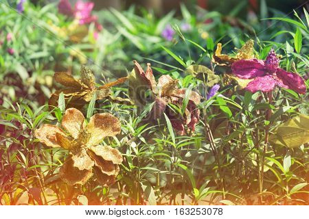 Beautiful plastic flowers decoration and nature garden blur background