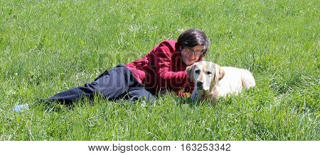 smiling young boy on the meadow in the mountains with his yellow Labrador Retriever dog