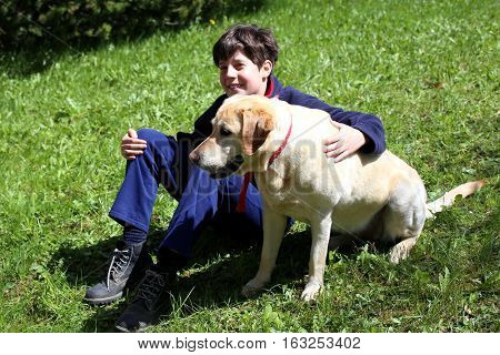 Smiling Little Boy With His Dog On The Lawn