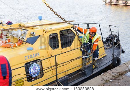 MOSCOW, RUSSIA - NOVEMBER 11, 2016: State Unitary Enterprise Mosvodostok performs recovery vessels on coastal winter parking. Worker pulling a chain sling.