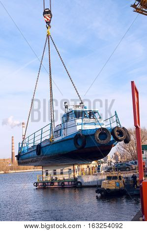 MOSCOW, RUSSIA - NOVEMBER 11, 2016: State Unitary Enterprise Mosvodostok performs recovery vessels on coastal winter parking. The ship rises from the water by a crane.