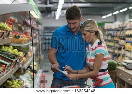 Couple Looking At The Grocery List In Supermarket