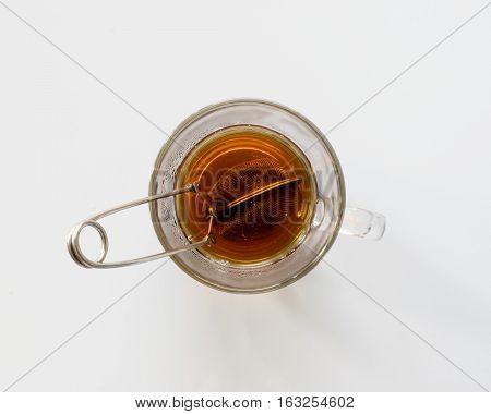 Tea strainer in glass cup of hot tea, top view.