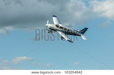 Single piston aircraft. Single-propeller aircraft flying over the blue sky at a small airport poster
