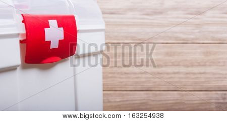 White Case with red clasp and a white cross. Wooden table background