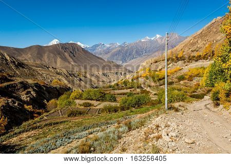 Mountain valley with terraced fields near town of Jhong. Annapurna circuit trek in Nepal.