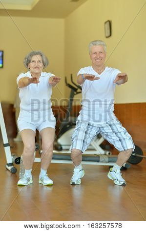 mature couple at the gym working out together