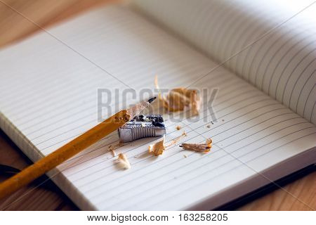 Quality image of Pencil & Sharpener kept on A Note book